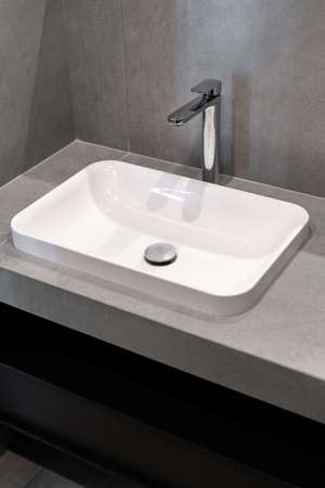 Concept of plumbing elements. Vertical photo of white sink and copy space on grey wall in new modern bathroom with contemporary interior design