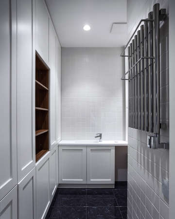 Vertical view of modern house with contemporary interior design in bathroom, wash basin on countertop, heated towel rail near wardrobe zone with shelves and drawers Stock Photo