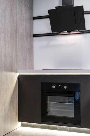 Side view of built in appliance, electric oven, cooking hood and hardwood cupboards. Vertical photo of element contemporary kitchen room with modern interior design Stock Photo
