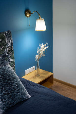 Vertical photo of modern bedroom in comfortable apartment with new interior, soft bed near blue wall, sconces lamp and flowers on bedside table