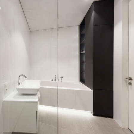 Modern house with contemporary interior design in bathroom, bathtub, wash basin on countertop and wardrobe closet against white copy space wall