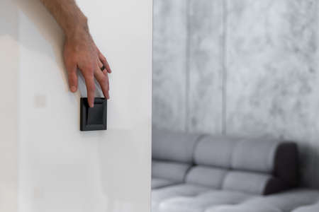 Cropped view of man hand turning light put finger on electric switch. Element of contemporary interior design with copy space wall against blurred living room on background