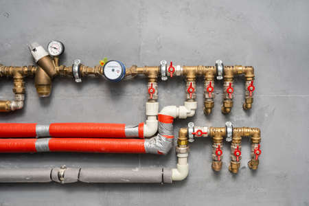Close up of element water pipes, plumbing stuff and valves on counter meter against wall in technical boiler room at new modern house