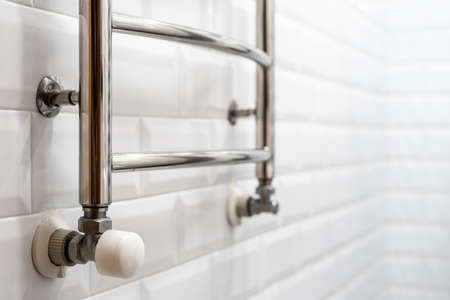 Selective focus on metallic electric heated towel rail against tiled wall on copy space background. Concept of new bathroom in modern apartment Stock Photo