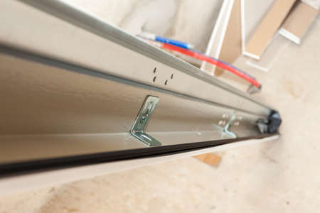 Concept of replacement details. Selective focus on metal rail at garage door system in new house under construction