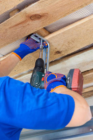 Vertical and cropped view of professional worker using electric screwdriver, install metal rail on wooden ceiling for garage door system. Building improvement and house under construction concept