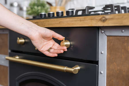 Cropped view of woman hand regulate button on built in oven equipment, standing near kitchen appliance in apartment with modern interior