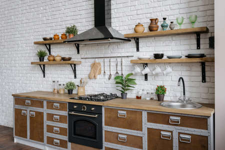 Side view of wooden kitchen facade in apartment with modern interior, new furniture, sink, gas stove, built in oven equipment, cooking hood, kitchenware supplies and green house plant decor