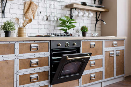 Modern built in oven with open door. Side view of wooden kitchen in contemporary interior house with new furniture, gas stove equipment, kitchenware supplies and houseplant in flower pot