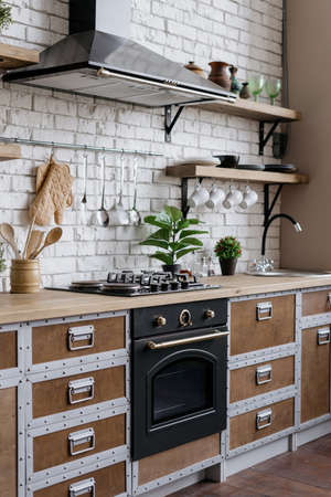 Vertical view element of wooden kitchen facade with new furniture, gas stove, built in oven equipment, cooking hood, kitchenware supplies and houseplant in flower pot in modern house interior Standard-Bild