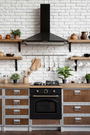 Gas stove, built in oven equipment, cooking hood, kitchenware supplies, green houseplant decor and new furniture against brick wall. Vertical view of wooden kitchen facade in modern interior house