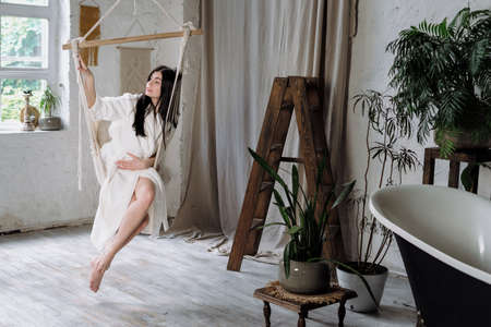 Tender and calm young adult female in white bathrobe sitting on a hanging swing at home, resting on weekend, enjoying morning, making dreaming face Banque d'images