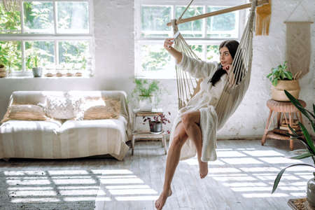Side view of young adult girl in bathrobe sitting on a hanging swing at home, using smartphone and making selfie photo on camera, posing, resting on weekend