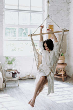 Vertical photo of happy young adult woman in bathrobe raised hands up, sitting on a hanging swing at home, laughing and spending free time in bedroom Banque d'images
