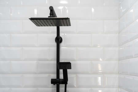 Close up of black shower head on holder against tiled wall on background. Concept of white bathroom in modern apartment Standard-Bild