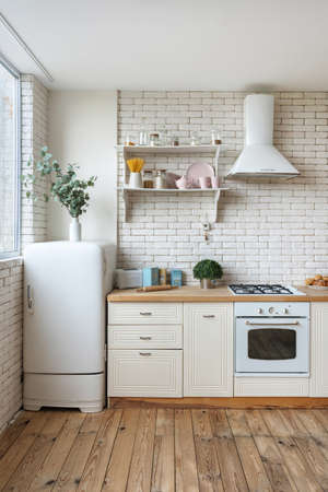 Vertical view of fridge, gas stove appliance, cooking hood, built in oven equipment, kitchenware supplies on shelves and green plants in kitchen at modern house with white interior design Imagens