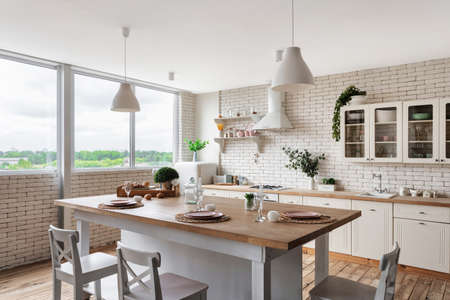 Side view of modern kitchen at home with white interior, tableware on dining table, cooking hood over gas stove appliance, sink, water tap, kitchenware supplies, green plants on cupboard furniture