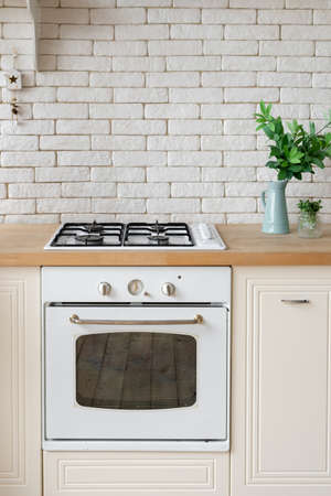 Vertical view of kitchen at modern house with white brick copy space wall, gas stove appliance, built in oven equipment and green plants on countertop surface