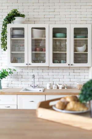 Selective focus on sink, water tap, kitchenware supplies on countertop, houseplants on cupboard furniture, blurred breakfast on table. Vertical view of kitchen at modern house with white interior