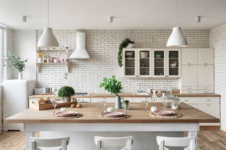 Modern kitchen at home with white interior, refrigerator, tableware on dining table, kitchenware supplies at shelf and green plants over cupboard furniture