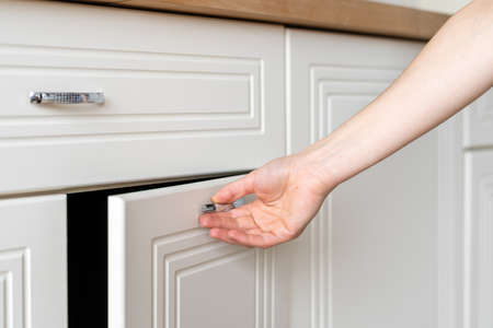Cropped view of woman hand open door at cupboard furniture standing on modern kitchen at home with white interior