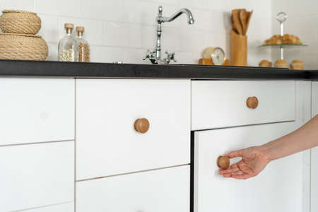 Cropped view of woman hand open cabinet door, pulling handle, standing at white modern kitchen in house with drawers under countertop Imagens