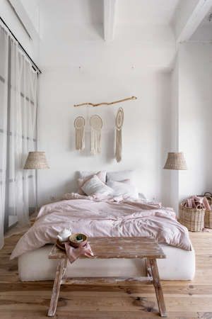 Vertical photo of morning in cozy bedroom with laundry basket near comfortable bed with crumpled duvet and pillows, macrame on white wall, home decor and teapot on bench