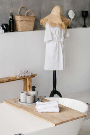 Vertical photo of white comfortable bath with clean rolled towels and house decor on wooden shelf against blurred bathrobe in bathroom on background Imagens