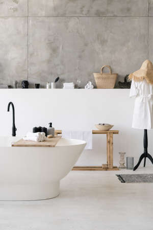 Vertical photo of at white contemporary house with modern bathroom interior, towels at wooden shelf on empty bathtub, bathrobe and house decor on background