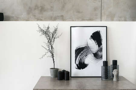 Table with home decor in living room. Modern interior house with abstract painting in frame, houseplant, candles, vase and decorative statuette against white concrete wall
