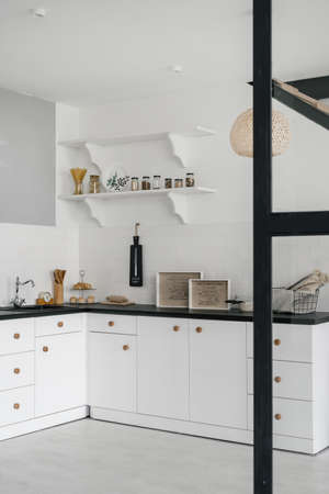 Vertical and side view photo of white modern kitchen with drawers over cabinet, sink, water tap, utensils on black countertop against tiled wall in room Imagens