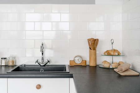 White kitchen in modern house with sink, water tap, utensils on black countertop over drawers against copy space tiled wall