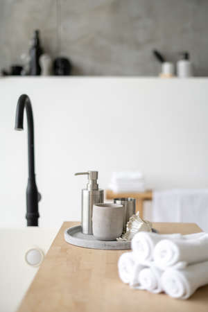 Vertical and selective focus on soap dispenser, candle, folded fresh towels at wooden shelf on white comfortable tub. Modern bathroom with house decor in contemporary interior