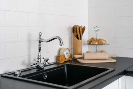 Close up of sink and silver water tap on black countertop against tiled wall. Utensils and baked croissant food at modern house with contemporary kitchen room