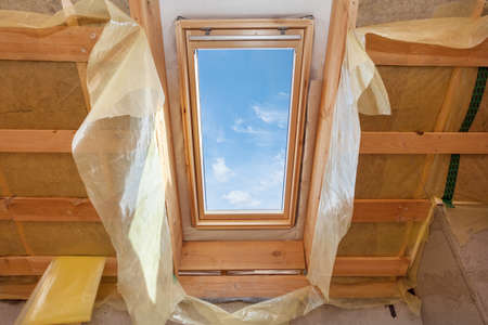 Concept of building improvements. Low angle view of house under construction, mansard with environmentally friendly and energy efficient skylight window against blue sky and wooden roof truss planks