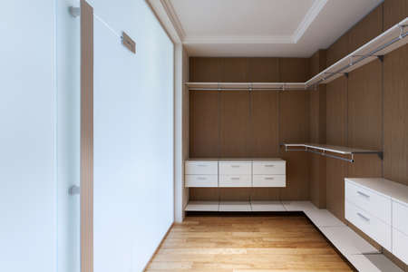 Modern house with contemporary interior design in bedroom. Empty wooden wardrobe closet, shelves and drawers in dressing room with glass doors