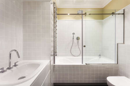 Element of modern house with contemporary interior design in bright bathroom, white tub, washstand on countertop, heated towel rail, and toilet bowl against copy space tiled wall Standard-Bild