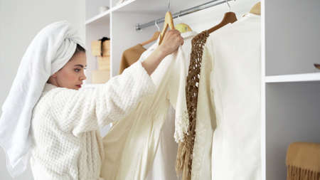 Side view of young adult woman standing in room at white bathrobe with towel on head, choosing clothes in wardrobe, making ponder face, checking quality of dress