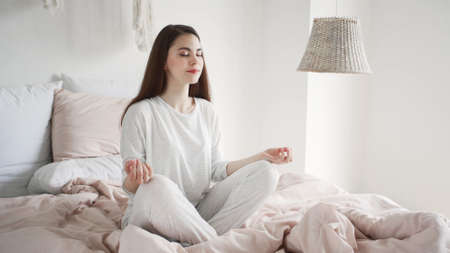 Mental health concept. Calm and dreamy young woman in pajamas sitting at meditation pose on bed in cozy bedroom, spending morning at home, resting and smiling nice