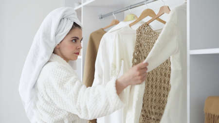 Morning routine concept. Side view of young female in white bathrobe with towel on head choosing clothes in wardrobe, dressing for work, making thoughtful face Stock fotó