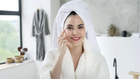 Skincare concept. Portrait of happy young woman in white bathrobe with towel on head applying cream on face, looking at camera, spending morning at bathroom, making skin care procedure Stock fotó