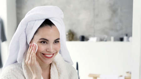 Portrait of happy young adult woman in white bathrobe and towel on head spending morning at bathroom, using cotton pad, removing makeup, smiling, standing against copy space background Stock fotó