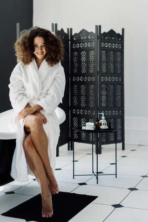 Concept of cosmetology and dermatology. Vertical and full length view of young and happy african american woman in bathrobe sitting on tub, spending morning in bathroom, looking at camera
