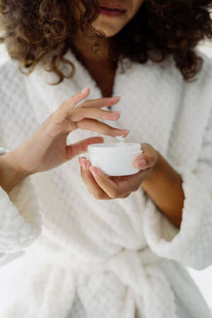 Concept of beauty procedure. Vertical cropped view of afro american woman holding cream in hands, standing in bathrobe and spending morning in bathroom Stock fotó