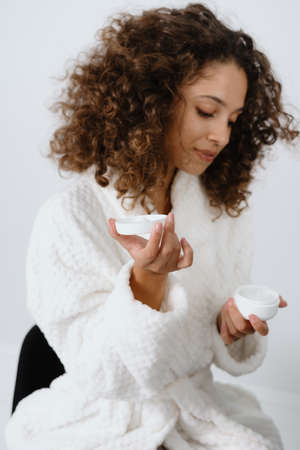 Concept of spa procedure at home. Vertical side view of calm young afro american woman in bathrobe holding container with moisturizing cream in hands, sitting at bathroom, making skincare routine