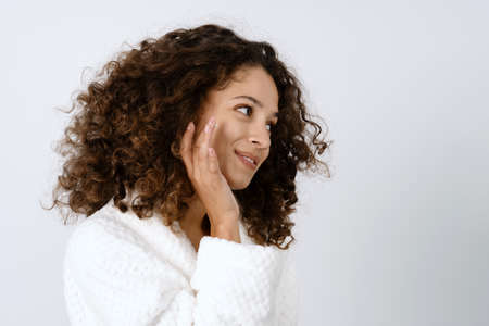 Skincare procedure concept. Side view portrait of smiling african american woman applying face cream on skin and sitting in bathrobe at bathroom against copy space background