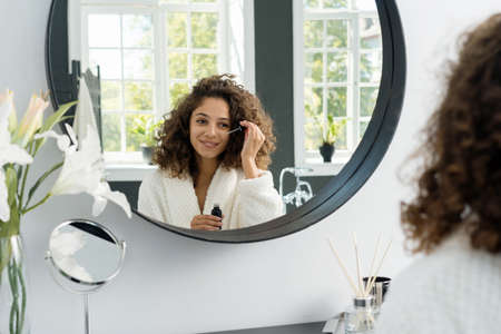 Concept of beauty procedure at home. Happy young adult african american woman holding pipette with anti wrinkle serum near eye, looking at mirror wearing in bathrobe, sitting at bathroom