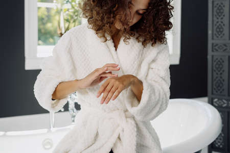 Concept of moisturizing procedure and everyday routine. African american woman applying cream on hands, standing in bathrobe, spending morning in bathroom Stock fotó