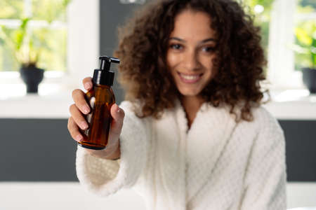 Beauty and wellness concept. Selective focus on bottle with dispenser in afro american woman hands. Happy african girl standing in bathrobe at bathroom, holding natural skincare or body care cosmetics