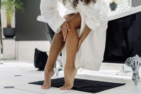 Concept of cosmetology and dermatology. Cropped view of african american woman in bathrobe touching soft legs after epilation and depilation procedure, spending morning in bathroom Stock fotó